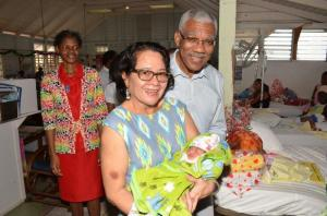 First Lady, Sandra Granger still has the touch. She is pictured here holding a little girl born to Cassie Baksh of Herstelling on December 23, as President David Granger looks on