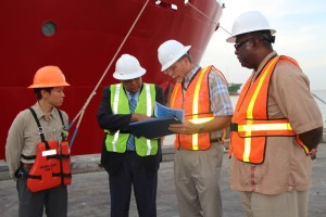 Mr. Dave Tuls, ESSO's Venture Manager, briefs Minister of Governance, Mr. Raphael Trotman; while Mr Patrick Lee (first, left) and Newell Dennison, Acting Commissioner, Guyana Geology and Mines Commission look on.