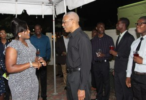President David Granger shares a light moment with Ms. Simona Broomes, one of the overseas- based Guyanese student at the event last evening and the daughter of the Minister within the Ministry of Social Protection.
