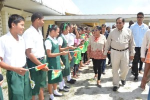 Prime Minister Minister Nagamootoo and Wife, Sita Nagamootoo being greeted by students of the Anna Regina Multilateral School on their arrival for the meeting.