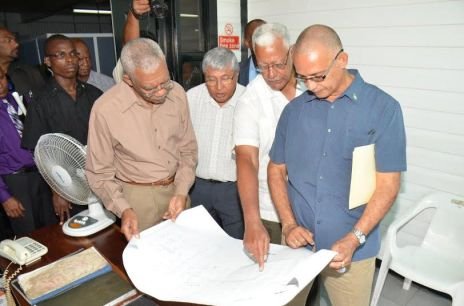 President Granger looks at a plan of the GuySuCo facility with (from right) Director of Protocol at the Ministry of the Presidency, Col. Francis A. Abraham, Minister of Agriculture, Mr. Noel Holder and Chief Executive Officer of GuySuCo, Mr. Errol Hanoman