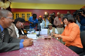 Prime Minister Portia Simpson Miller (right), about to hand in her nomination fee as a candidate for the constituency of South Western St. Andrew. (Photo: JIS)