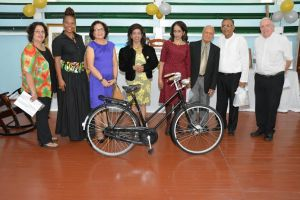 Third to sixth from left: First Lady, Mrs. Sandra Granger, Ms. Kella Ramsaroop, Ms. Pamela Ramsaroop and Mr. Yesu Persaud. Bishop Francis Alleyne, OSB, is pictured first from right. The Ramsaroops have owned the Humber bicycle displayed since 1940.