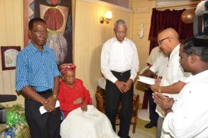 : President David Granger with Mrs. Olive Blackmore as her relatives and members of her church say a prayer. (GINA photo)