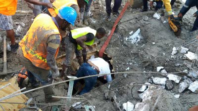 These men check under the rubble for workers who may have been trapped after the collapse of the building at the construction site.