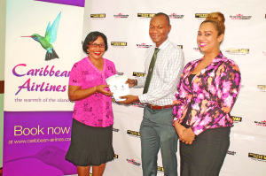 From left to right: Winner Nandaney Budram receives her plain tickets from Caribbean Airlines' representative Dion Inniss, while Western Union's Reena Williams looks on
