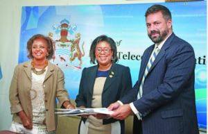 Telecommunication Minister Cathy Hughes (centre), UNDP Resident Representative Kadija Musa and Depecon representative Stephen Dieter share the signed agreement