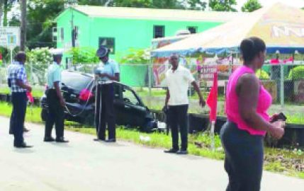 The driver of the motor car (in pink) at the scene along with investigators after hitting two St Lucian boys