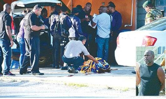 "A DMO checks the body of one of the men shot along with Selwyn ""Robocop"" Alexis, inset, in Enterprise, Chaguanas, yesterday. Alexis and one of his customers were killed in an ambush by a man, who was also killed. (TT Guardian photo)"