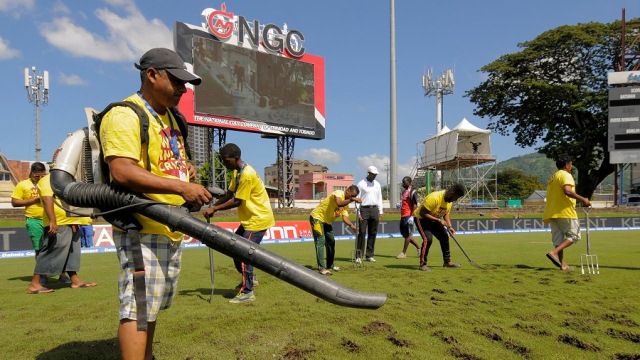 Ground staff at Queen's Park Oval dug up the outfield in a bid to get it to dry out(AFP photo)