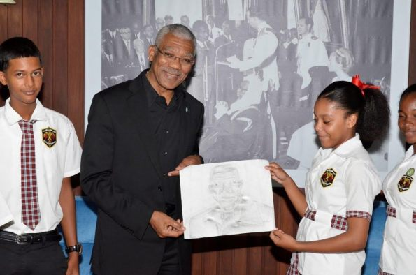 Hannah Monroe hands over the portrait she drew with charcoal to President David Granger, earlier today at the Ministry of the Presidency. (MOTP photo)