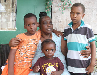Gloria Hinkson hugs her grandchildren—Daniel, five, Aliyah, three and Lennon, seven—at their Point Fortin home yesterday, hours after where their father, David Hinkson, was killed on Wednesday night. PHOTO: RISHI RAGOONATH