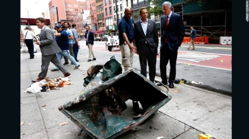 New York Mayor Bill de Blasio, right, and New York Governor Andrew Cuomo, second right, look over the mangled remains of a dumpster on Sunday, September 18, while touring the site of an explosion in New York's Chelsea neighborhood that injured 29 people.