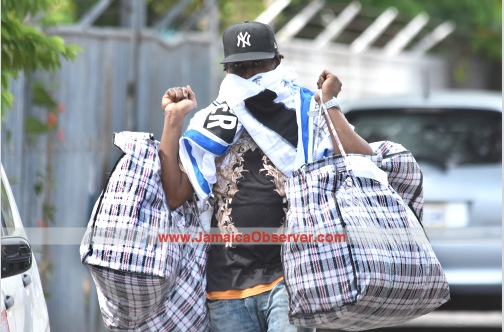 This man carries large bags, presumably bearing his belongings, as he leaves the Mobile Reserve after being processed by the Jamaican police, yesterday. (Photo: Michael Gordon)