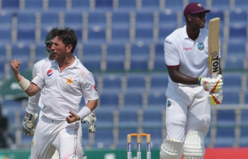Pakistani spinner Yasir Shah (L) celebrates after taking the wicket of the West Indies' cricket captain Jason Holder (R) on the final day of the second Test between Pakistan and the West Indies at the Sheikh Zayed Cricket Stadium in Abu Dhabi on October 25, 2016. (Photo: AFP)