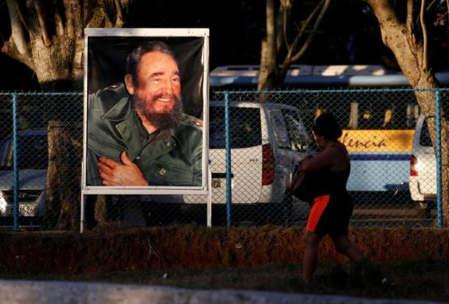A woman walks past a photograph of former President Fidel Castro after the announcement of his death, in Havana, Cuba, November 27, 2016. REUTERS/Stringer