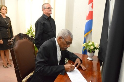 President David Granger signs the Book of Condolence, which has been opened at the Cuban Embassy in Georgetown, for the late Fidel Castro (Ministry of the Presidency photo)