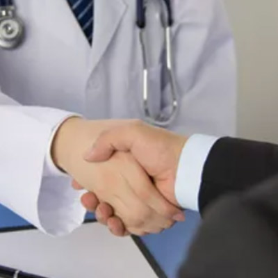 Healthcare executive and physician shaking hands as part of a high value network agreement
