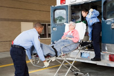 Paramedics putting senior woman into ambulance at a safety net hospital