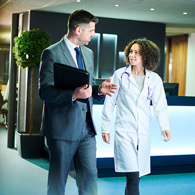 Male business man and female doctor talking about referral coordination while walking together in the office.