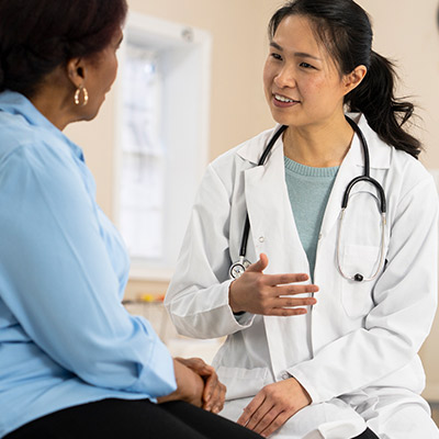 A senior woman of african descent is having a conversation with her female doctor.