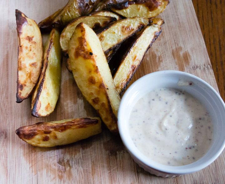 oven roasted fries with dijon dipping sauce on a wooden serving board