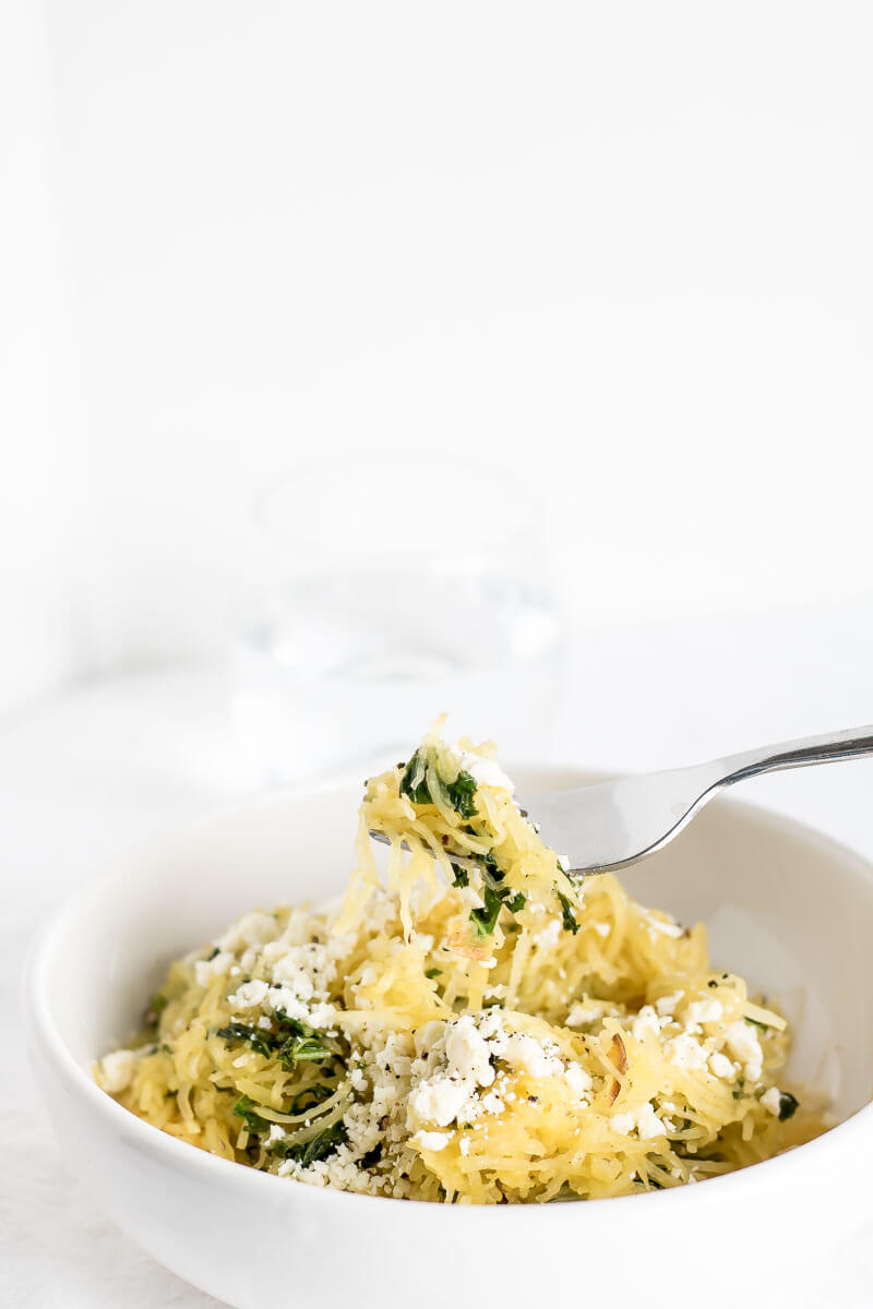 A bowl of spaghetti squash tossed with kale and feta with a fork taking a bite