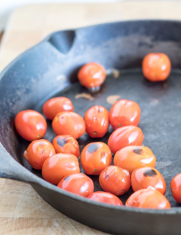 blackened cherry tomatoes in a cast iron skillet