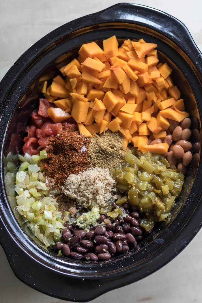 Slowcooker full of chili ingredients - butternut squash, beans, chilis, tomatoes and spices