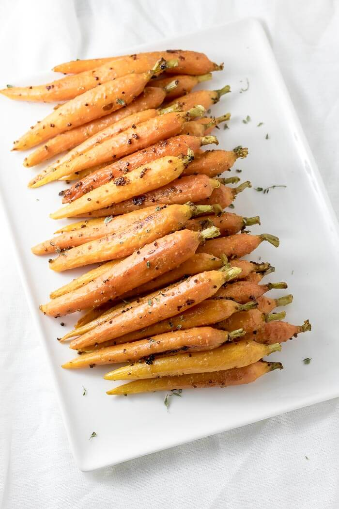 maple glazed carrots on a plater sprinkled with thyme