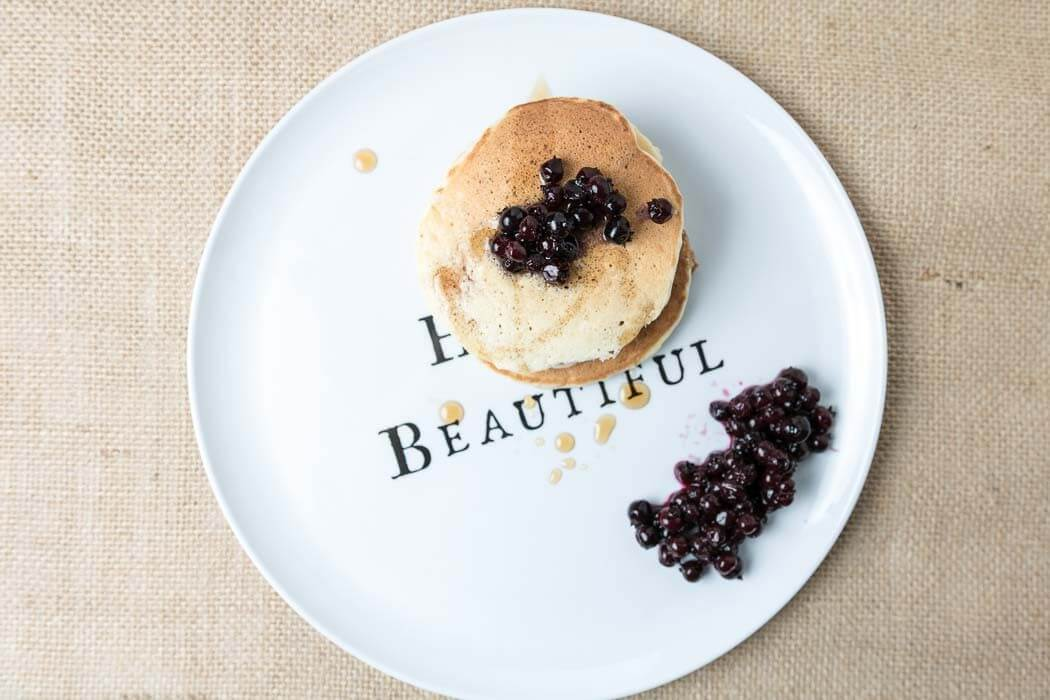 top view of banana pancakes with blueberries on beautiful plate