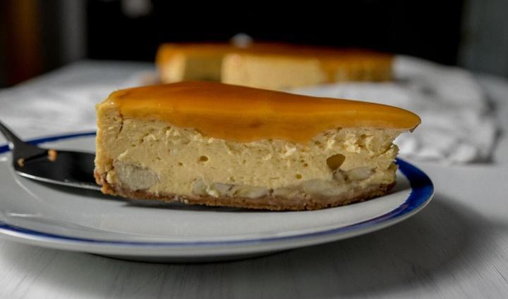 Slice of Bananas Foster Cheesecake on a plate. Banana layered inside cheesecake