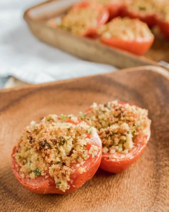 a serving of baked tomatoes on a wooden plate