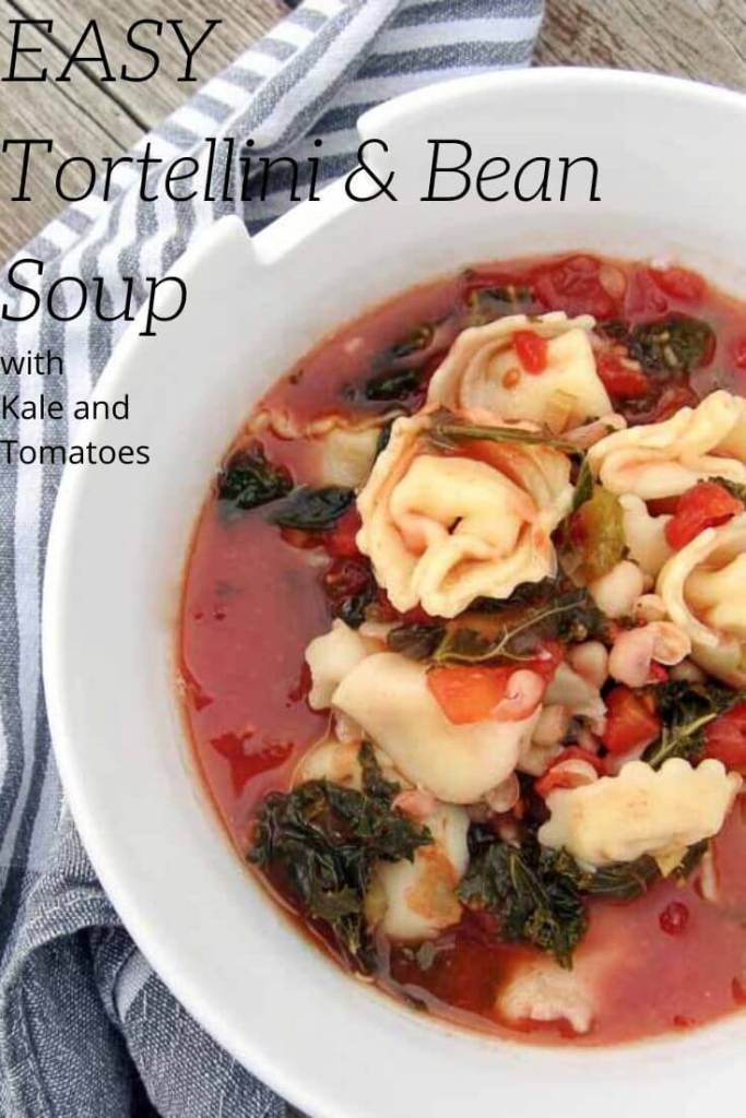 totellini soup with beans and kale in a white bowl with a striped napkin