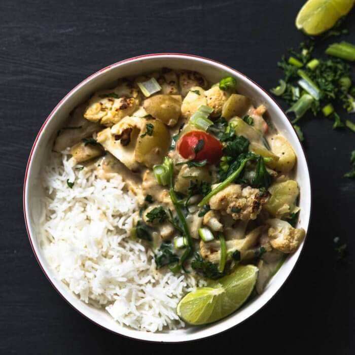 potato curry in a bowl with rice and greens on a black backgroud, lime and cilantro in background