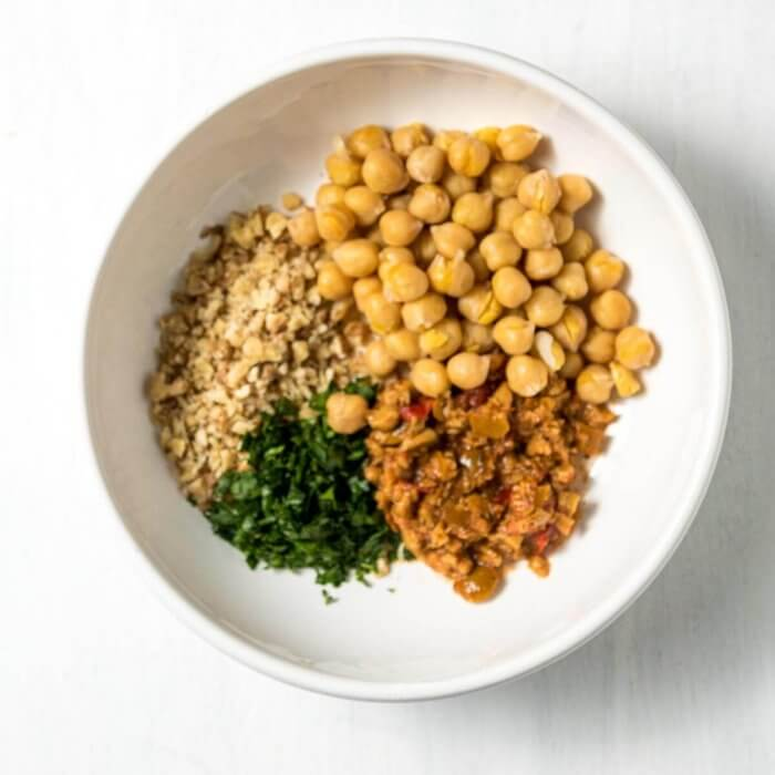 chickpeas, tapenade, chopped walnuts and parsley in a white dish for an easy weeknight pasta dish