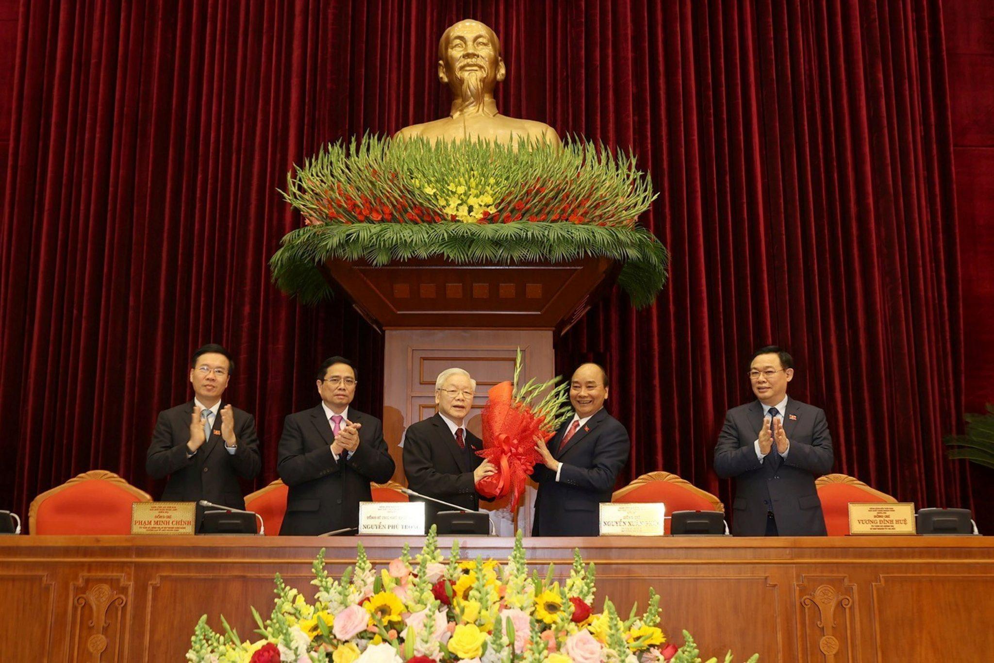 Vietnam's President and General Secretary of the Communist Party Nguyen Phu Trong (3rd L) receives flowers from Prime Minister Nguyen Xuan Phuc after he was re-elected as party chief for a 3rd term during the 13th national congress of the ruling communist party in Hanoi, Vietnam, 31 January 2021. L-R are politburo members Vo Van Thuong, Pham Minh Chinh and Vuong Dinh Hue (Photo:Reuters).