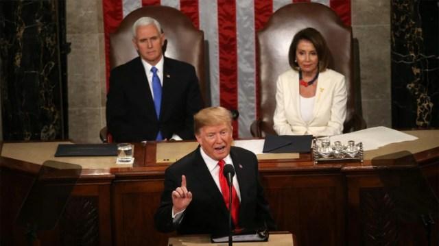 Trump y atrás, a su izquierda, Nancy Pelosi