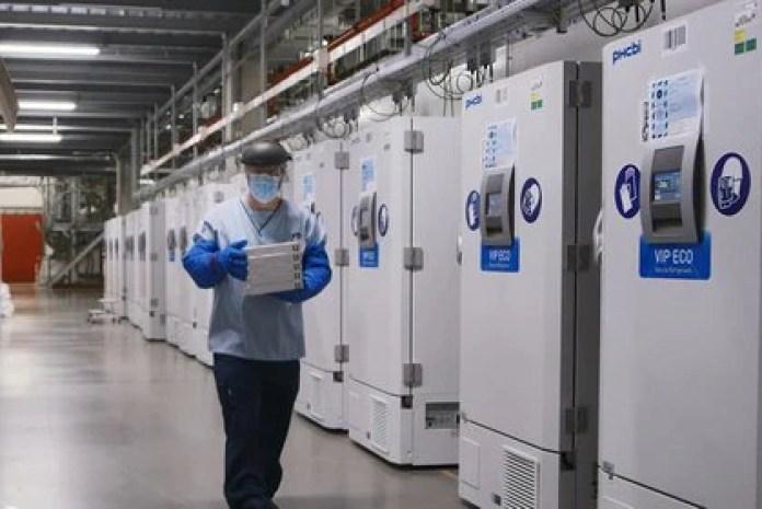 Un trabajador pasa por una línea de congeladores que contiene la vacuna candidata al COVID-19 (Pfizer/a través de REUTERS/Foto de archivo)