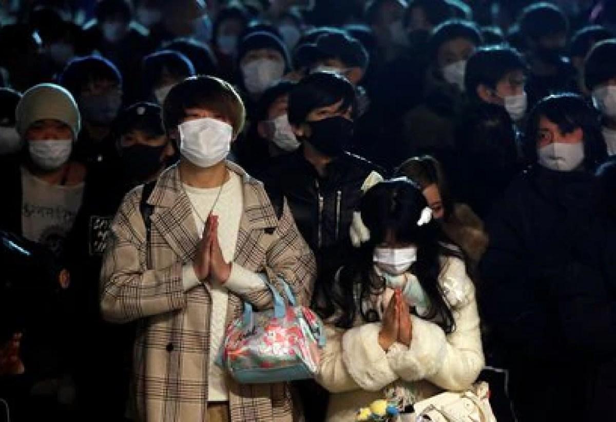 Personas con mascarilla rezan por la llegada del nuevo año (Reuters/ Issei Kato)