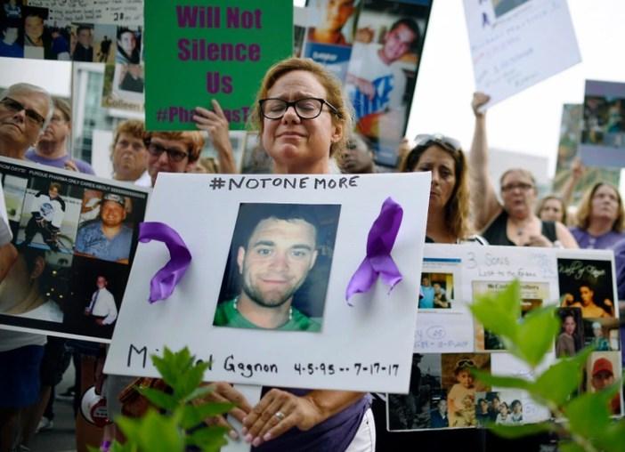 Una mujer sostiene una foto de una personas víctima de los opiodes. (AP Photo/Jessica Hill, File)