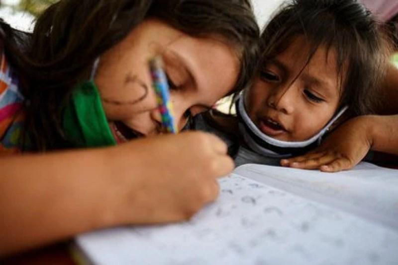 Dos niños haciendo cuentas en una tarea de matemática en la improvisada escuela de Denisse Toala en el barrio Realidad de Dios, en Guayaquil. (REUTERS/Santiago Arcos)