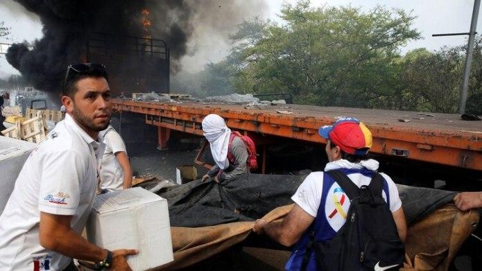 Venezolanos intentan vaciar uno de los camiones con alimentos y remedios que fue quemado por orden de Nicolás Maduro (Reuters)