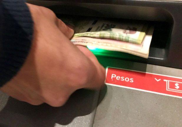 Foto de archivo. Un hombre retira pesos argentinos de un cajero automático de un banco en el distrito financiero de Buenos Aires. 30 de agosto de 2018. REUTERS/Marcos Brindicci