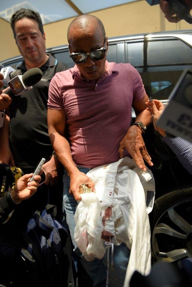 Eliezer Salvador, quien dice haber llevado a David Ortiz al hospital tras ser herido de bala un día antes, muestra los pantalones ensangrentados del expelotero, el lunes 10 de junio de 2019, al hablar con la prensa frente a la clínica (AP Foto/Roberto Guzmán)