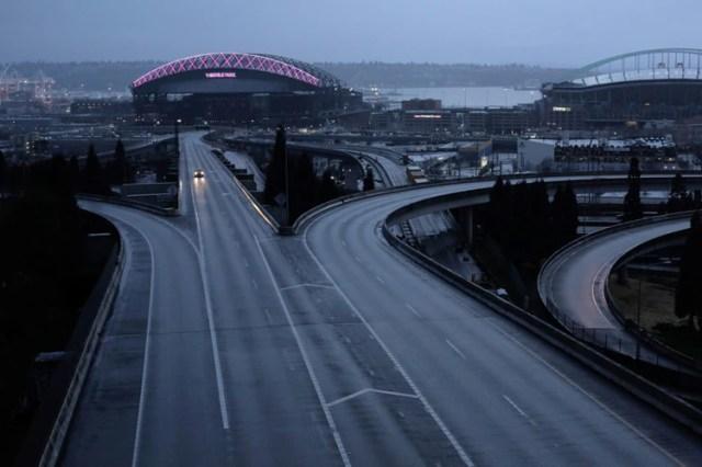 Un automóvil en solitario se mueve a lo largo de una carretera vacía durante el brote de la enfermedad por coronavirus en Seattle, Washington (Reuters)