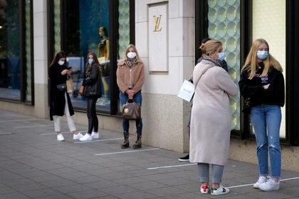 Personas en una cola de protección en el exterior de la tienda de Louis Vuitton en Frankfurt, Alemania, el 28 de octubre de 2020, REUTERS/Kai Pfaffenbach