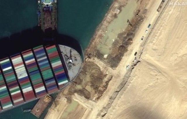 Una vista del equipo de movimiento de tierra que excava arena cerca de la proa del barco de contenedores Ever Given, en el Canal de Suez en esta imagen satelital de Maxar Technologies tomada el 27 de marzo de 2021 (REUTERS)