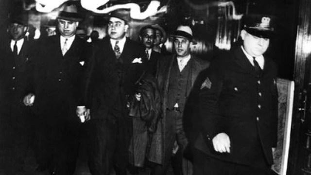 Alphonse Capone es escoltado por agentes federales luego de ser condenado por evasión impositiva en los tribunales de Chicago (Shutterstock)