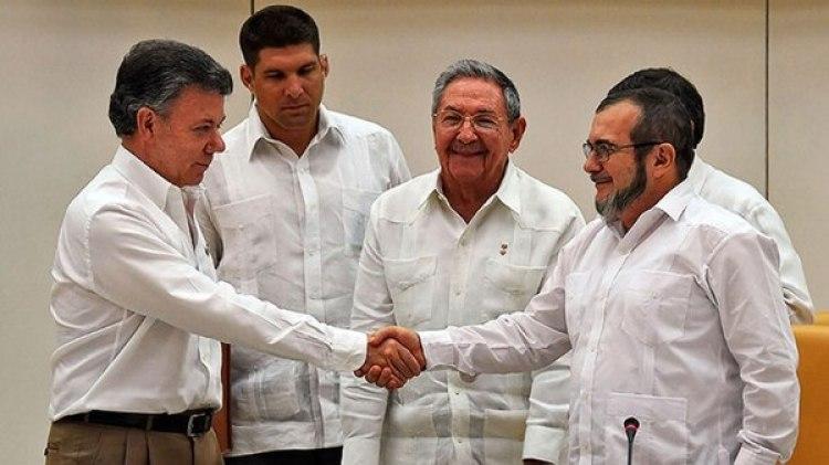 Juan Manuel Santos estrecha la mano del jefe de las FARC, Timochenko, frente a un sonriente Raúl Castro